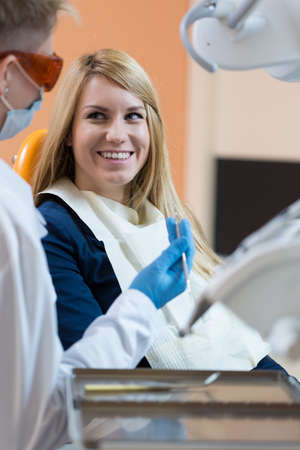 stomatologist: Young smiling woman and her visit at stomatologist Stock Photo