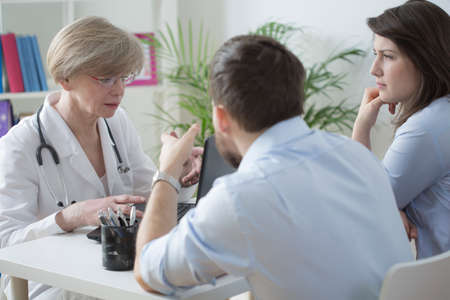 color consultation: Young infertile couple on medical consultation with female gynecologist Stock Photo
