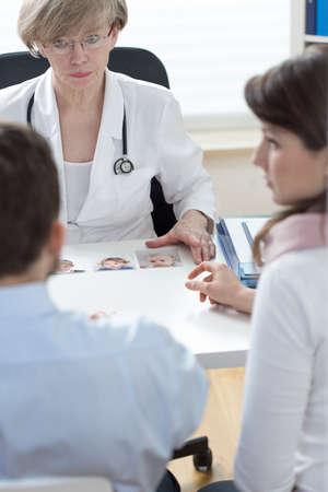 consulta médica: Pareja infértil y hembra médico descontentos hablando in vitro