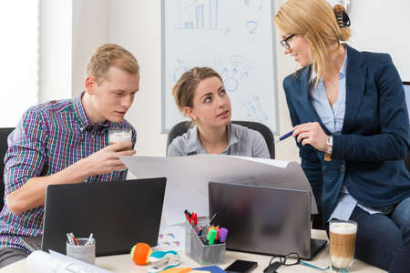 open plan: Office workers talking about guidelines to project Stock Photo