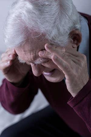obsolescence: Senior with chronic headache Stock Photo