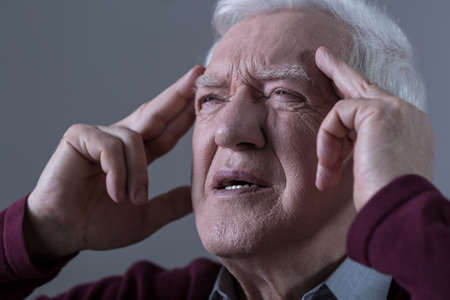 pensionary: Old man holding his temples with opressive pain