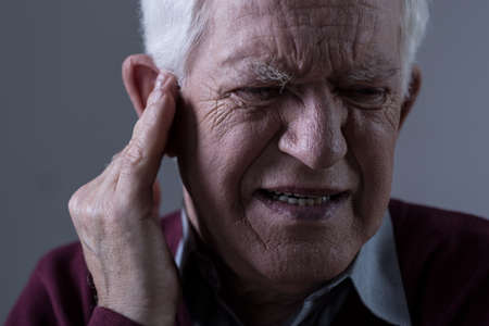 耳鳴りに苦しむ老人 写真素材