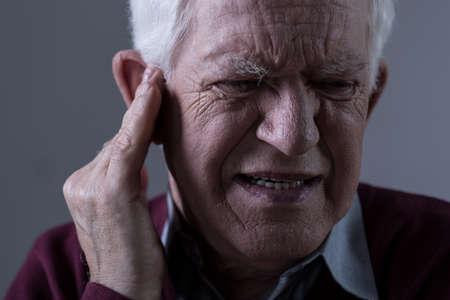 oreja: Anciano sufren de tinnitus Foto de archivo