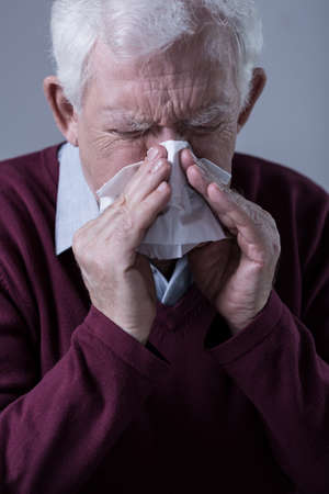 catarrh: Old man with infection blowing his nose Stock Photo
