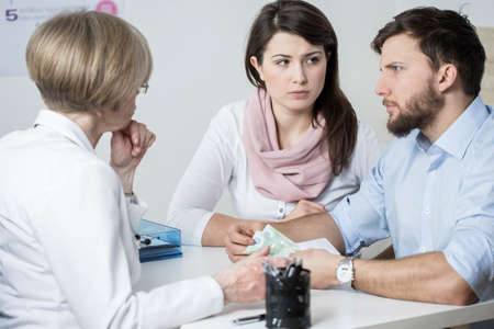 medical doctors: Young worried couple paying to experienced doctor for visit Stock Photo