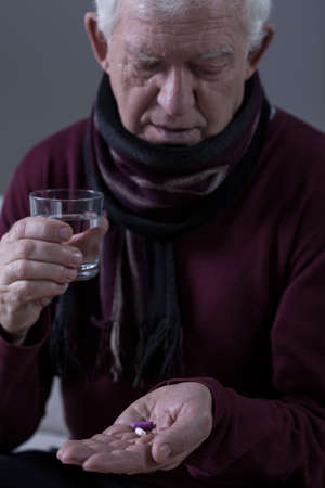 catarrh: Elderly man with infection taking medicine Stock Photo