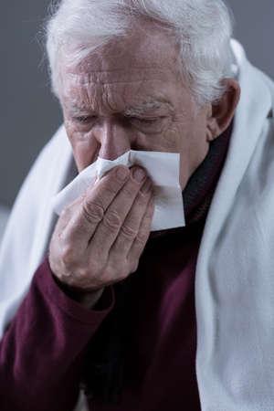 catarrh: Cold elderly man blowing his nose