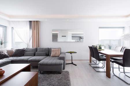 Geräumige up-to-date Wohnzimmer mit großen Esstisch aus Holz Standard-Bild
