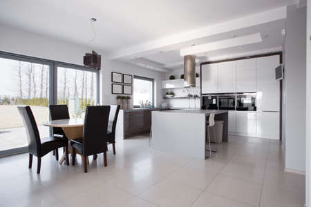 Spacious white kitchen connected with dining hall Stockfoto