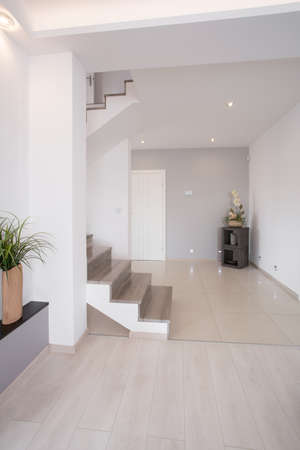stairs interior: White clean hallway with wooden stairs on the first floor