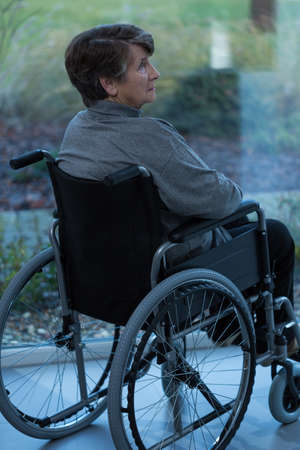 pensionary: Elderly lonely and sad women in a wheelchair Stock Photo