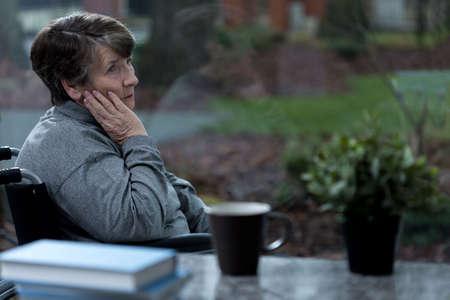 Depressed women sitting in a wheelchair at home Standard-Bild