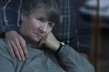 pensionary: Senior sad woman is supported by her grandson