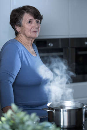 pensionary: Thoughtful elderly women standing in the kitchen Stock Photo