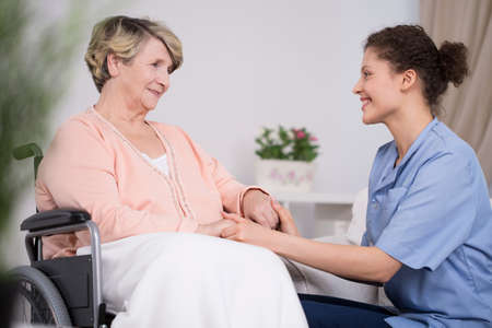 Young pretty thoughtful nurse and older lady on wheelchair