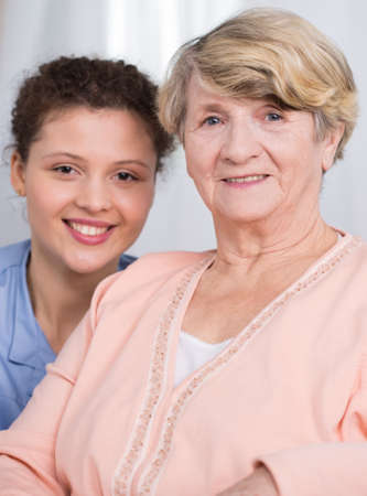 female doctor: Pretty smiling young carer and her friendly female ward Stock Photo