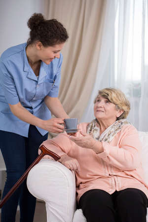 color therapist: Helpful young caregiver servicing the tea to older lady