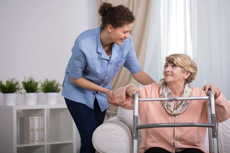 lesionado: Mujer mayor con el caminante herido tratando de ponerse de pie
