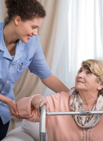 careful: Careful young female physiotherapist and older disabled woman