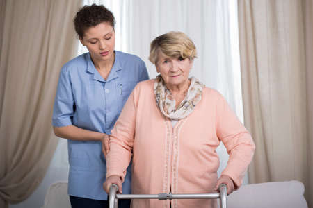 color therapist: Aged disabled lady with walker and her helpful caregiver