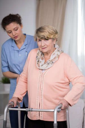 color therapist: Female carer helping older woman with handicap Stock Photo