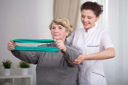 Elderly active woman exercising with young physiotherapist