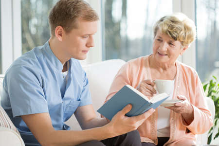 retirement  age: Reading a book and drinking tea at a nursing home