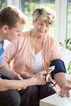 sphygmomanometer: Young male nurse taking blood pressure