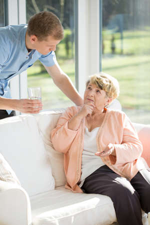 caring for: Male nurse caring for an elderly patient