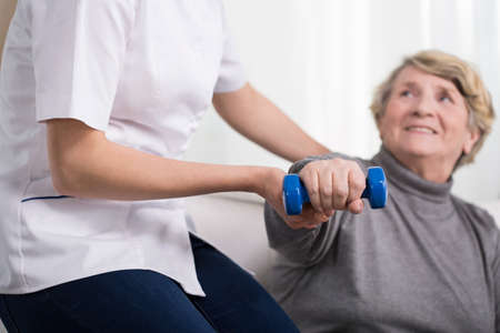 Aged exercising woman and female physiotherapists help