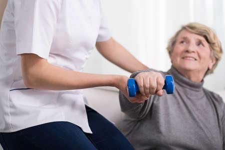 Aged uitoefening vrouw en hulp vrouwelijke fysiotherapeut Stockfoto