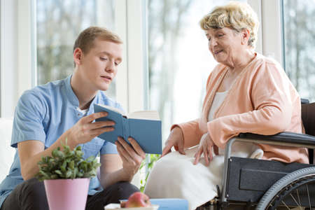 Nurse reading a book with old woman on a wheelchair Stock Photo