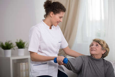 care home: Young pretty therapist exercising with older female patient