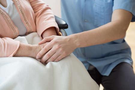 manos sosteniendo: Enfermera de la mano de una mujer en una silla de ruedas Foto de archivo