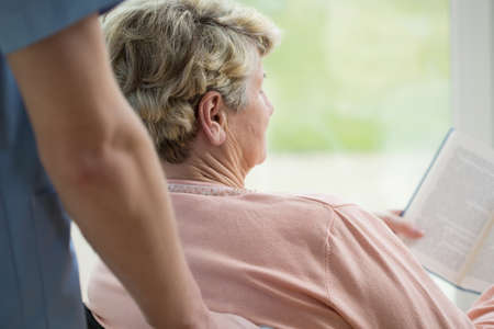 home nursing: Old woman on a wheelchair reading book