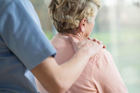Verpleegkundige zetten hand op de schouder van de bejaarde vrouw
