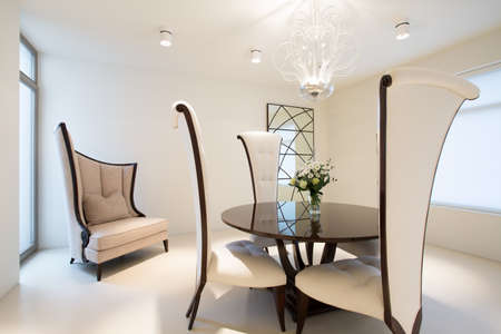 Sophisticated apartment with glass coffee table and fancy chairs