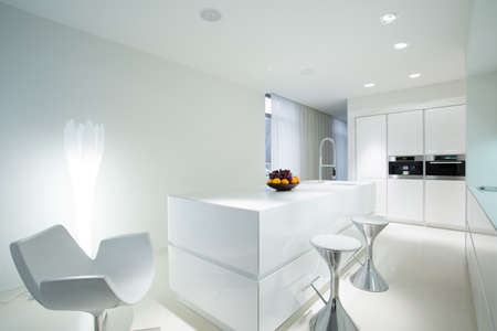 a kitchen: Modern white kitchen with extravagant dining space Stock Photo