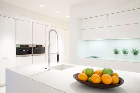 contemporary kitchen: Fruit in a bowl on the marble island in white kitchen Stock Photo