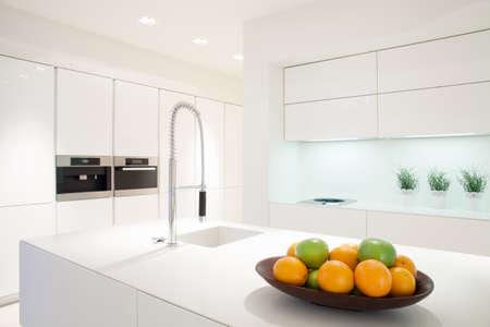Fruit in een kom op de marmeren eiland in witte keuken