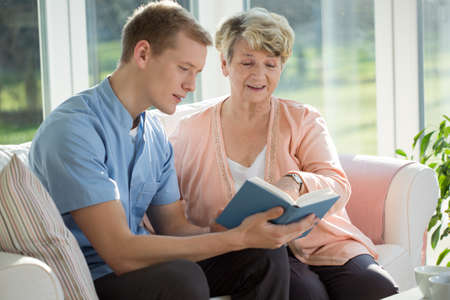home care nurse: Young male nurse reading to his elderly patient Stock Photo