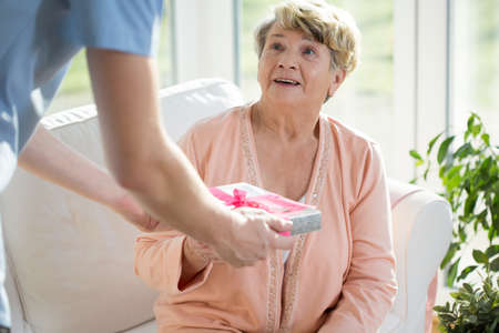 old sofa: Nurse giving a gift to an elderly woman Stock Photo