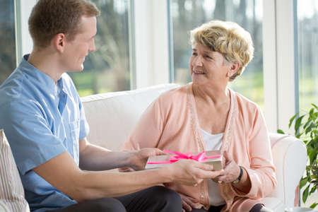vejez feliz: La mujer mayor est� recibiendo un regalo de un enfermero Foto de archivo