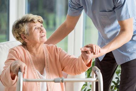 vejez feliz: La mujer mayor se ayuda con caminar de una enfermera Foto de archivo