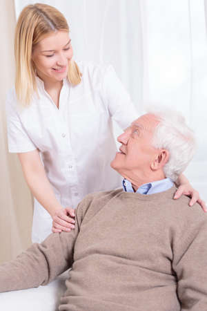 color therapist: Young beautiful helpful caregiver and her older ward Stock Photo