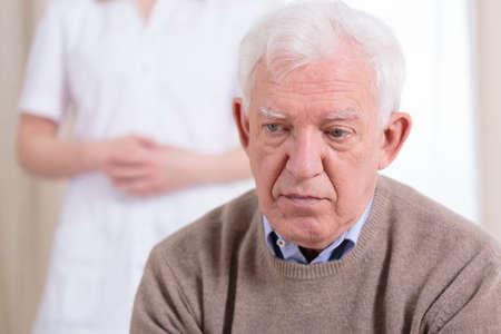 pielęgniarki: Smutny starszy samotny mężczyzna siedzi w domu opieki