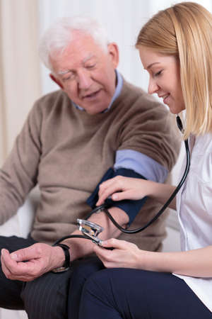 2 people at home: Pretty experienced nurse measuring the older mans blood pressure