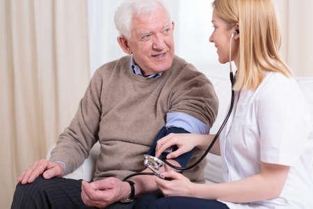 Jonge lachende zorgverlener controleren hypertensie haar oudere patiënt Stockfoto