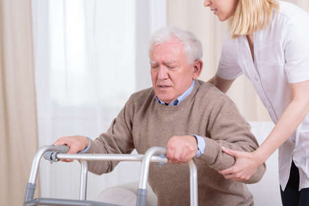 color therapist: Careful nurse helping senior man with walker to stand up